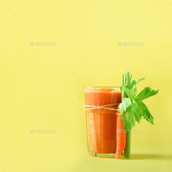 Orange carrot juice with carrots, celery on yellow background. Square crop. Fresh vegetable smothie - Stock Photo - Images