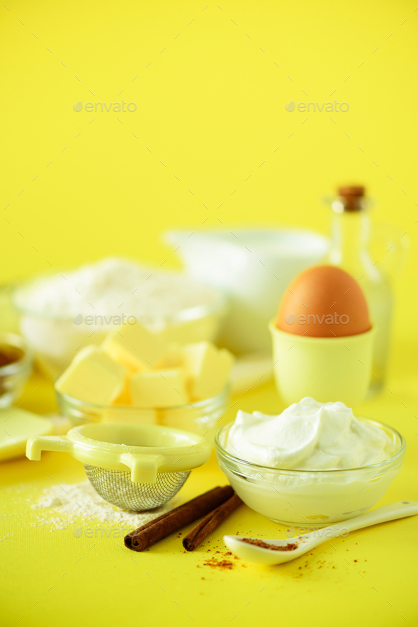 Healthy baking ingredients - butter, sugar, flour, eggs, oil, spoon, rolling pin milk over yellow - Stock Photo - Images
