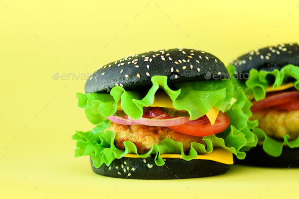 Fast food - juicy hamburgers on yellow background. Take away meal. Unhealthy diet concept with copy - Stock Photo - Images