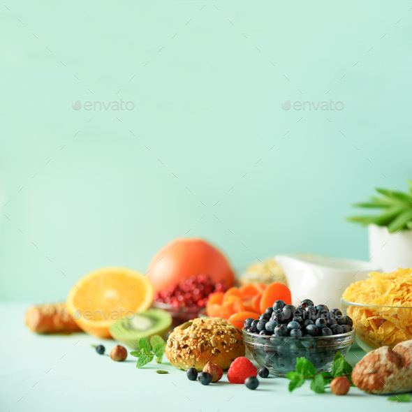 Healthy breakfast ingredients. Square crop. Oat and corn flakes, eggs, nuts, fruits, berries, toast - Stock Photo - Images