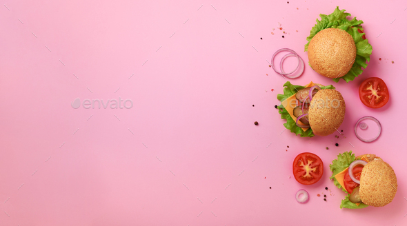 Fast food, unhealthy diet concept. Juicy homemade burgers, tomatoes, cheese, onion, cucumber and - Stock Photo - Images
