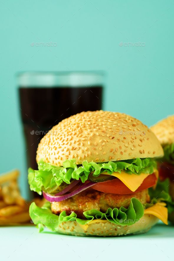 Fast food concept. Juicy homemade hamburgers on blue background. Take away meal. Unhealthy diet - Stock Photo - Images