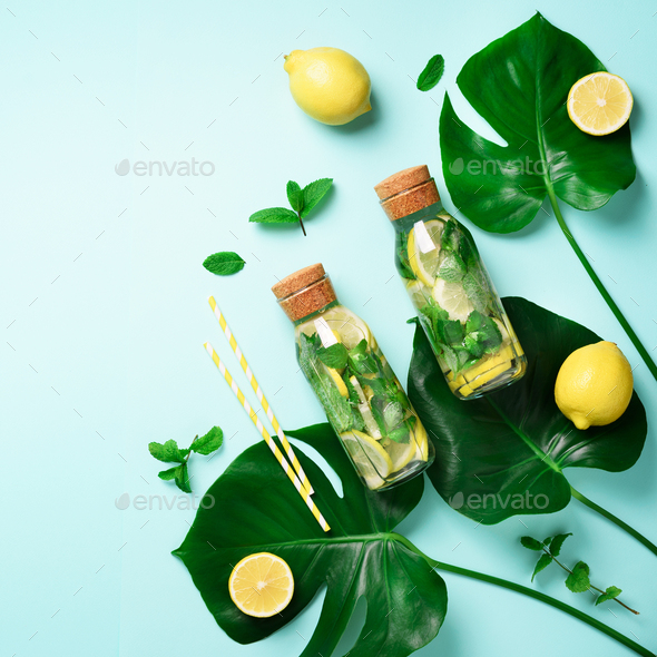 Bottle of detox water with mint, lemon and tropical monstera leaves on blue background. Square crop - Stock Photo - Images