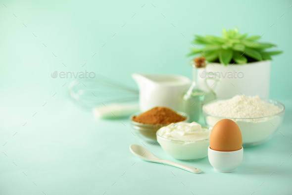 Time to bake. Baking ingredients - butter, sugar, flour, eggs, oil, spoon, brush, whisk, milk over - Stock Photo - Images
