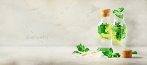 Detox water with mint, lemon and tropical monstera leaves on grey background. Banner with copy space - Stock Photo - Images