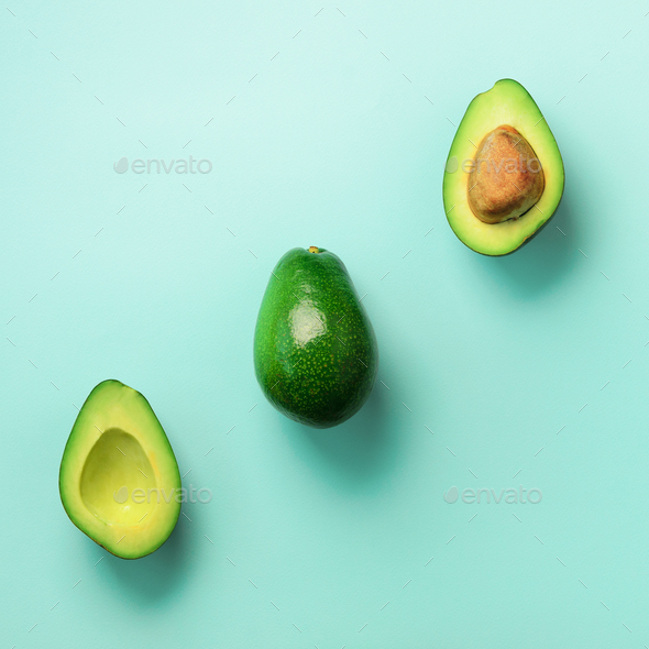 Organic avocado with seed, avocado halves and whole fruits on blue background. Top view. Pop art - Stock Photo - Images