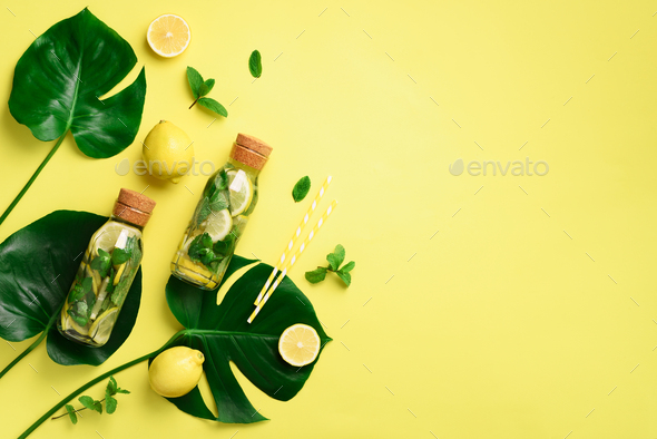 Bottle of detox water with mint, lemon and tropical monstera leaves on yellow background. Flat lay - Stock Photo - Images
