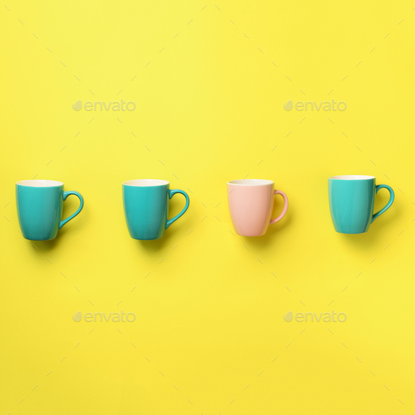 Pattern from blue and pink cups over yellow background. Square crop. Birthday party celebration - Stock Photo - Images