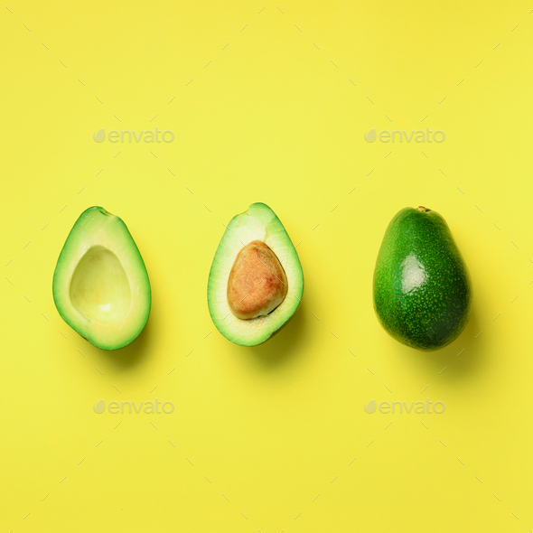 Organic avocado with seed, avocado halves and whole fruits on yellow background. Top view. Square - Stock Photo - Images