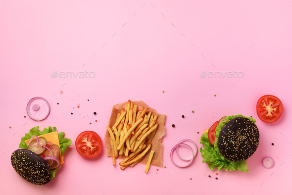 Black burger, french fries potatoes, tomatoes, cheese, onion, cucumber and lettuce on pink - Stock Photo - Images