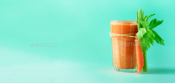 Organic carrot juice with carrots, celery on blue background. Fresh vegetable smothie in glass - Stock Photo - Images