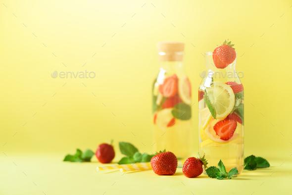Strawberry detox water with mint, lemon on yellow background. Citrus lemonade. Banner. Summer fruit - Stock Photo - Images