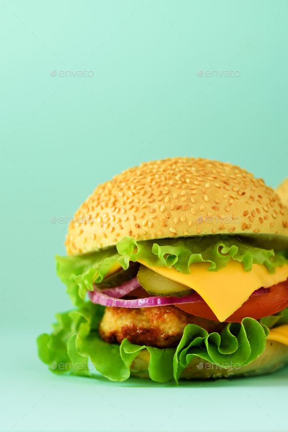 Macro view of tasty burger with beef, cheese, lettuce, onion, tomatoes on blue background. Close up - Stock Photo - Images