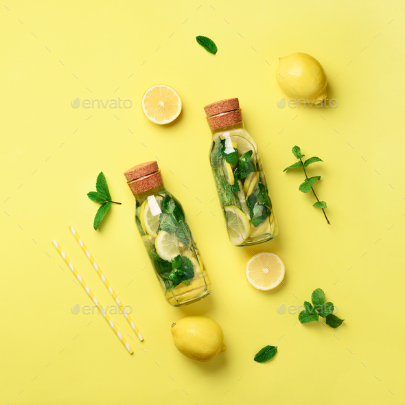 Bottle of detox water with mint, lemon on yellow background. Flat lay. Square crop. Citrus lemonade - Stock Photo - Images