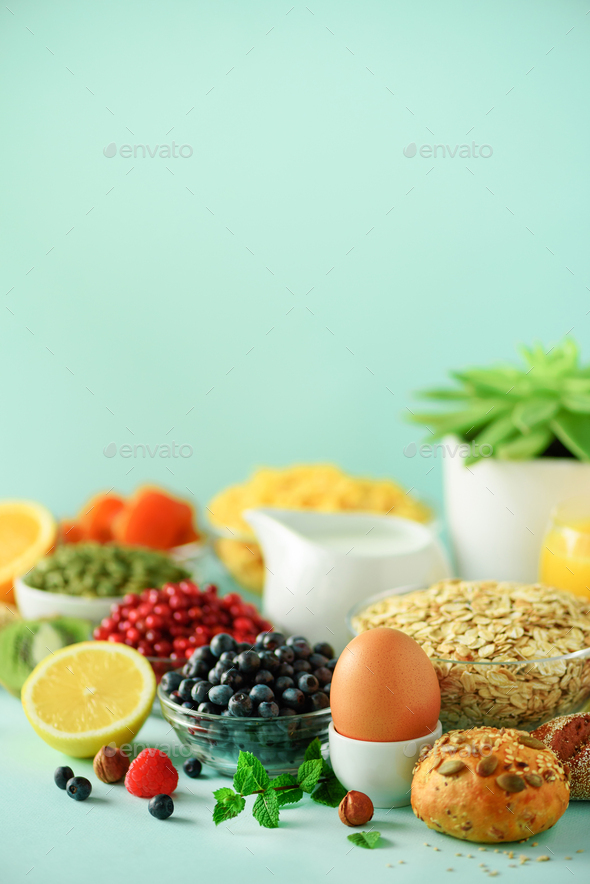 Corn flakes with milk, fresh berries, yogurt, boiled egg, nuts, fruits, orange, banana, peach for - Stock Photo - Images