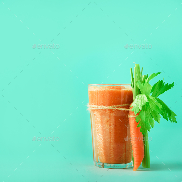 Fresh organic carrot juice with carrots, celery on blue background. Square crop. Vegetable smothie - Stock Photo - Images