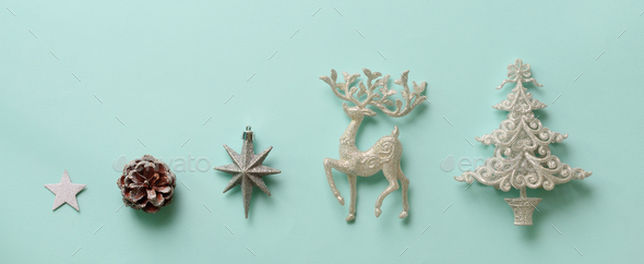 Silver Christmas decoration - deer, fir-tree, stars, cone on blue background with copy space - Stock Photo - Images