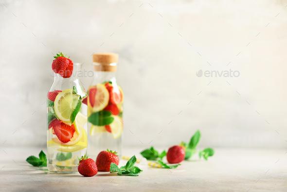 Citrus and strawberry lemonade with mint, lemon on grey background. Detox drink. Summer fruit - Stock Photo - Images