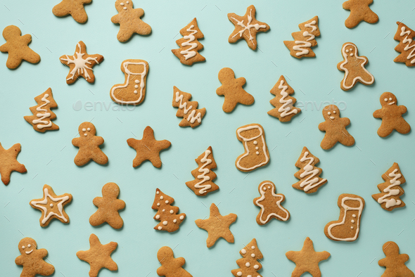 Homemade christmas cookies on blue background. Pattern of gingerbread men, snowflake, star, fir-tree - Stock Photo - Images