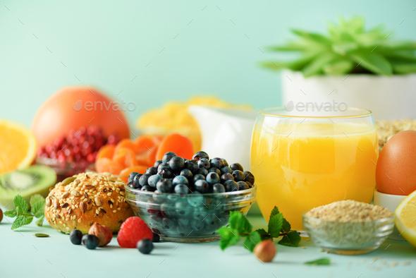 Orange juice, fresh berries, milk, yogurt, boiled egg, nuts, fruits, banana, peach for breakfast on - Stock Photo - Images
