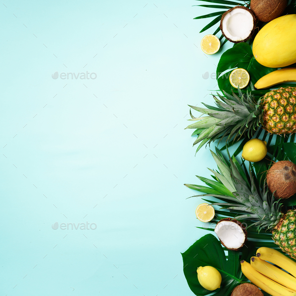Exotic pineapples, ripe coconuts, banana, melon, lemon, tropical palm and monstera leaves on blue - Stock Photo - Images