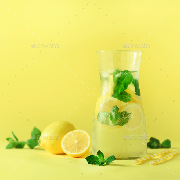 Fresh summer fruits water or lemonade with mint, ice, lemon on yellow background. Square crop. Copy - Stock Photo - Images