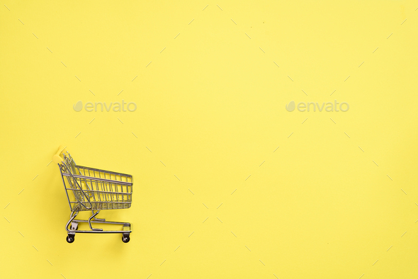 Shopping cart on yellow background. Minimalism style. Creative design. Top view with copy space - Stock Photo - Images