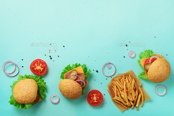 Tasty burgers with beef, tomato, cheese, onion, cucumber and lettuce on blue background. Top view - Stock Photo - Images