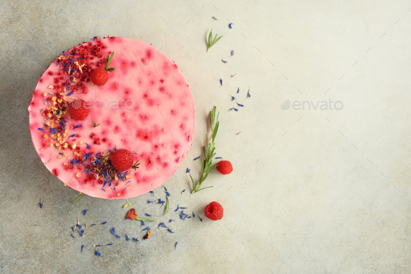 Delicious raspberry cake with fresh berries, rosemary and dry flowers on gray concrete background - Stock Photo - Images