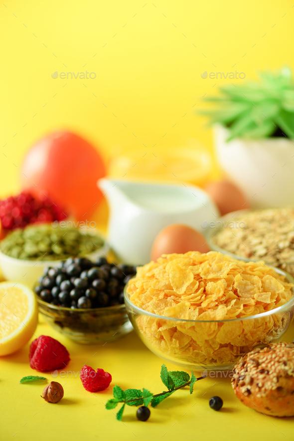 Corn cereal, muesli, milk, berries, orange juice, yogurt, boiled egg, nuts, fruits, banana, peach - Stock Photo - Images