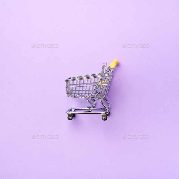Shopping cart on purple background. Minimalism style. Square crop. Creative design. Top view with - Stock Photo - Images