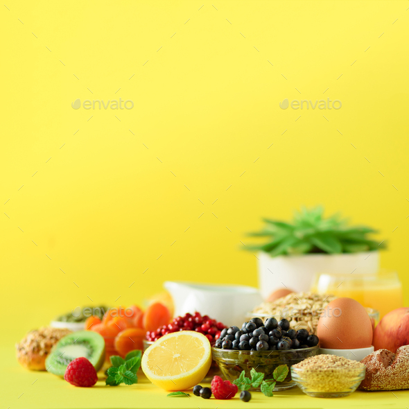Organic breakfast ingredients. Square crop. Oat and corn flakes, eggs, nuts, fruits, berries, toast - Stock Photo - Images