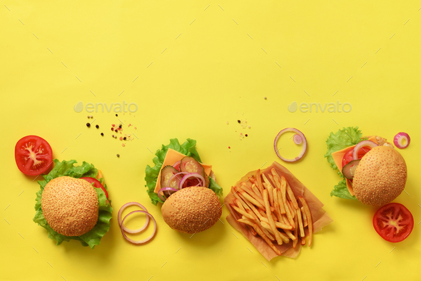 Tasty burgers with beef, tomato, cheese, onion, cucumber and lettuce on yellow background. Top view - Stock Photo - Images