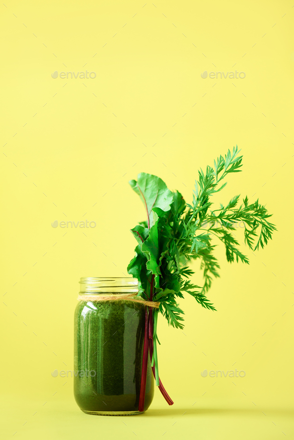 Organic smoothie with beet greens and carrot tops on yellow background, copy space. Summer vegan - Stock Photo - Images