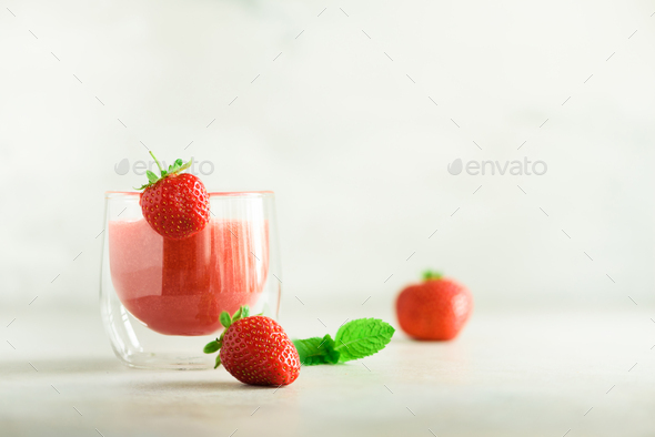 Red strawberry milkshake in glass on grey background with copy space. Summer food concept, vegan - Stock Photo - Images