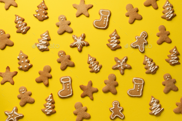 Homemade christmas cookies on yellow background. Pattern of gingerbread men, snowflake, star, fir - Stock Photo - Images