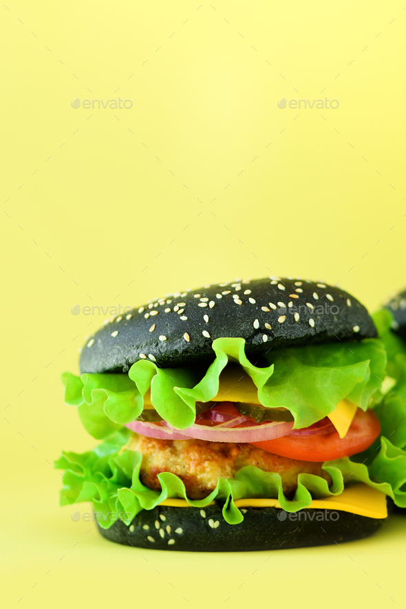 Fresh meat black burgers on yellow background. Take away meal. Fast food concept. Unhealthy diet - Stock Photo - Images