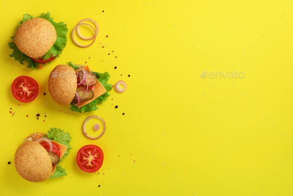 Delicious burgers, cheese, lettuce, onion, tomatoes on yellow background. Close up banner. Unhealthy - Stock Photo - Images