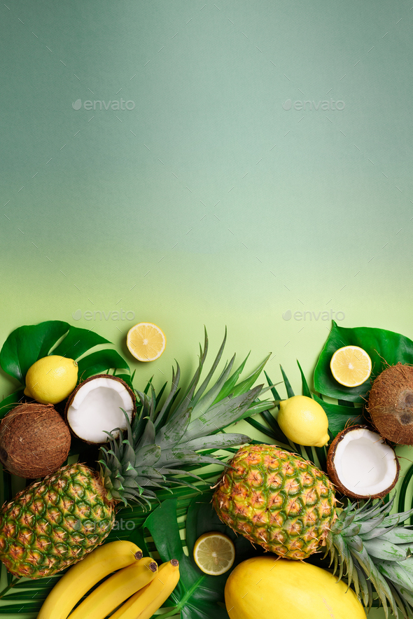 Exotic pineapples, coconuts, banana, melon, lemon, tropical palm and monstera leaves on green - Stock Photo - Images