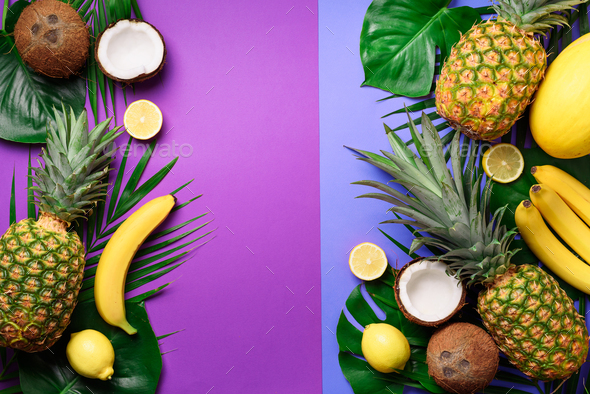 Exotic pineapples, coconuts, banana, melon, lemon, tropical palm and green monstera leaves on purple - Stock Photo - Images
