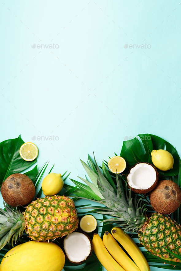 Exotic pineapples, ripe coconuts, banana, melon, lemon, tropical palm and green monstera leaves on - Stock Photo - Images