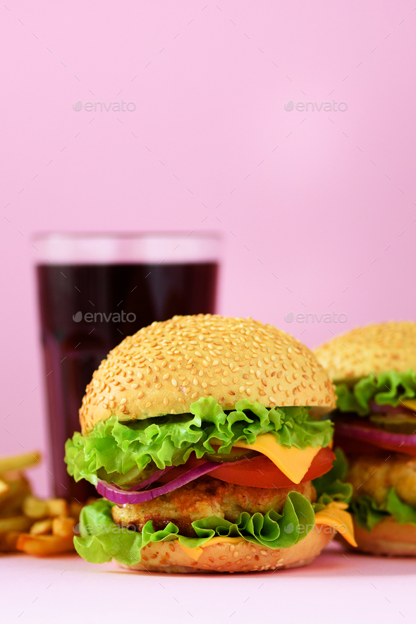 Fast food frame. Delicious meat burgers on pink background. Take away meal. Unhealthy diet concept - Stock Photo - Images