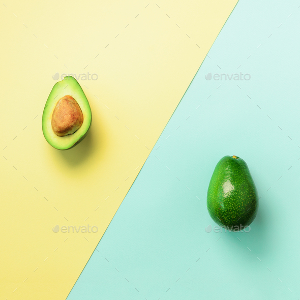 Avocado sliced with seed, whole fruit on blue and yellow background. Top view. Pop art design - Stock Photo - Images