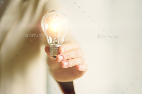 Woman hand holding light bulb on cream background with copy space. Creative idea, new business plan - Stock Photo - Images