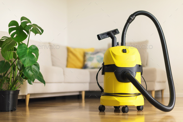 Yellow modern vacuum cleaner in living room. Copy space. Flat clean vacuuming concept. Green - Stock Photo - Images