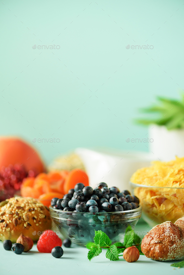 Delicious breakfast ingredients. Corn flakes, nuts, fruits, berries, milk, yogurt, orange, banana - Stock Photo - Images