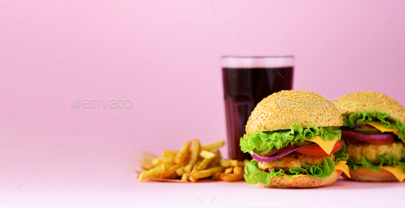 Fast food banner. Juicy meat burgers, french fries potatoes and cola drink on pink background. Take - Stock Photo - Images