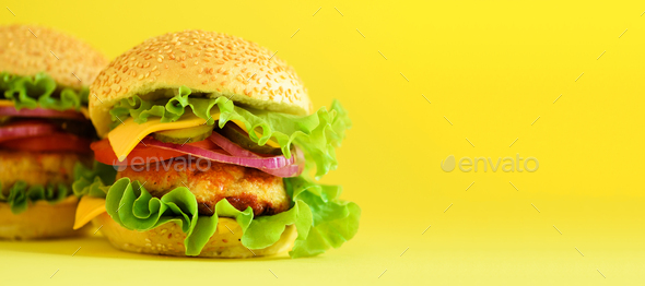 Fast food banner. Juicy meat burgers with cheese, lettuce on yellow background. Take away meal - Stock Photo - Images