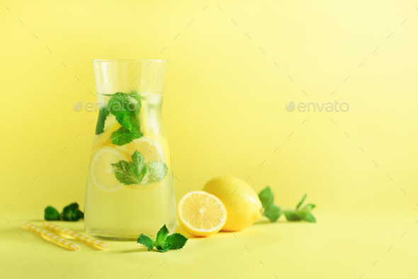 Detox water with mint, lemon on yellow background. Banner with copy space, sunlight bokeh. Citrus - Stock Photo - Images