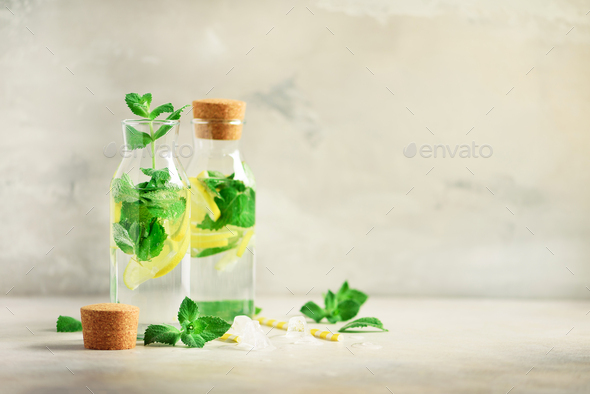 Bottle of detox water with mint, lemon on grey background. Citrus lemonade. Summer fruit infused - Stock Photo - Images